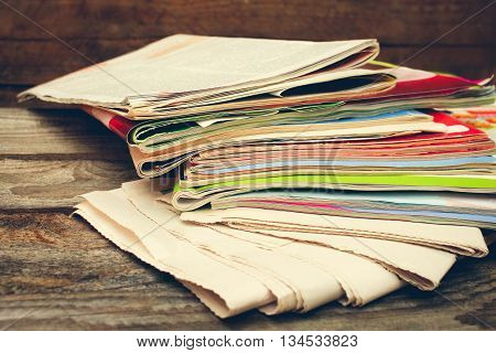 Magazines and newspapers on old wood background. Toned image
