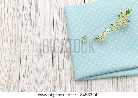Napkin with polka dots and twig with white flowers on a wooden background. Copy space