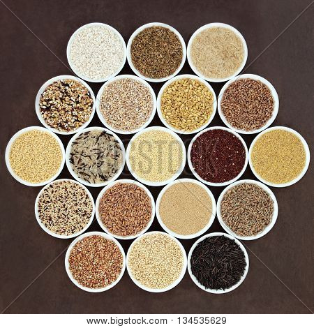 Grain health food in round porcelain bowls over lokta paper background.