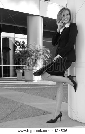 Business Woman Leaning On Pillar Talking On Cell