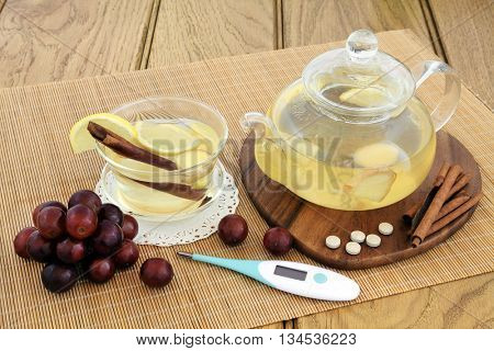 Hot lemon, honey and ginger drink for cold remedy in a glass tea cup and teapot with red grapes, cinnamon stick spice, ginseng vitamin tablets and thermometer on bamboo over oak background.