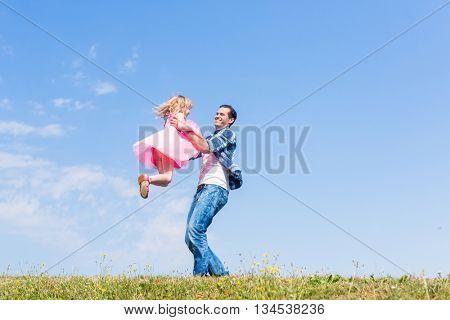 Father lifts daughter over head on summer meadow