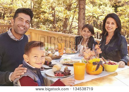 Happy family at a table on a deck in a forest look to camera