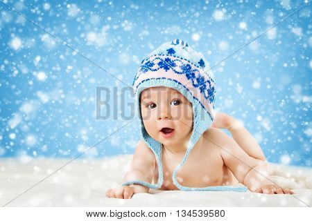 Eight month old baby in knitted winter hat lying on soft blanket with blue background and falling snow