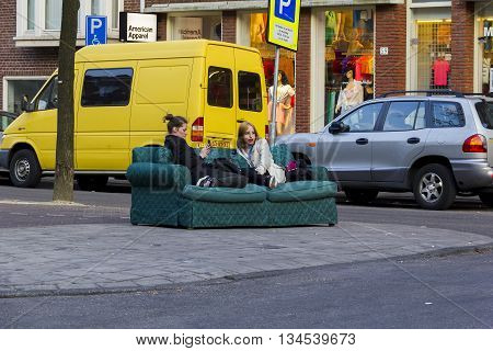 AMSTERDAM, NETHERLANDS - MAY 5, 2013: At the weekend residents staged a porch on a street with an old couch.