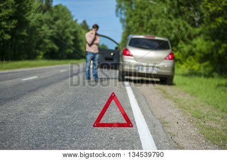 Red triangle warning sign closeup man calling to a car assistance after breakdown. Selective focus