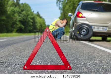 Sad man after car breakdown broken car and spare wheel on the roadside. Focus on red triangle warning sign