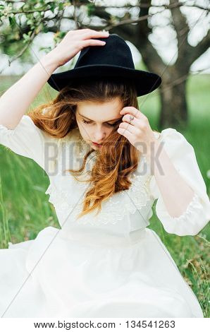 Young Girl In A White Dress And Black Hat In The In The White Fl