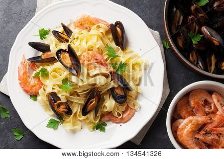 Pasta with seafood on stone table. Mussels and prawns. Top view