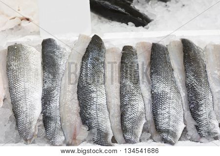 Fresh sea bass fillets on ice, closeup