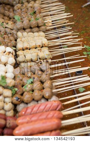 Soft Focus  Meatballs On Sticks, Dipped In Sweet Chili Sauce At A Market In Thailand