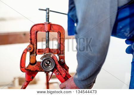 worker, handyman using wrench at industrial plumbing