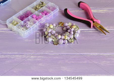 Elegant lilac bracelet made of acrylic beads and metal decorative elements. Stylish accessory for girls and women. Different beads and materials in a plastic box, pliers. Set for handmade jewelry