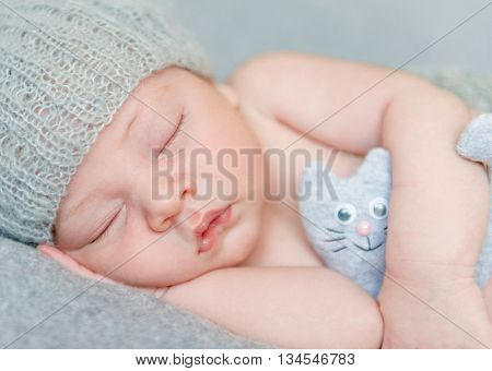 sweet sleeping newborn baby in gray hat with toy, close-up