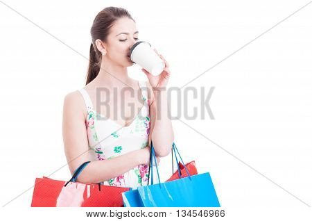 Lady Carrying Shopping Bags Taking A Sip From Takeaway Coffee
