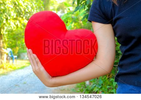 Red heart hold in a woman hand