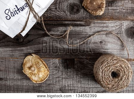 Close up of package with organic dried shiitake japanese mushrooms on wood background. Top view