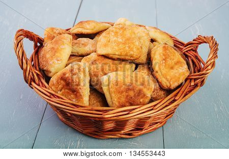 delicious homemade biscuits in wicker basket on vintage wooden table