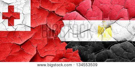 Tonga flag with egypt flag on a grunge cracked wall