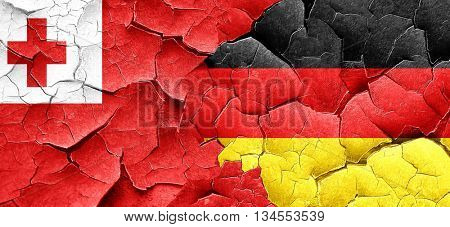 Tonga flag with Germany flag on a grunge cracked wall