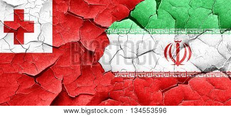 Tonga flag with Iran flag on a grunge cracked wall