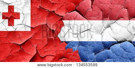 Tonga flag with Netherlands flag on a grunge cracked wall