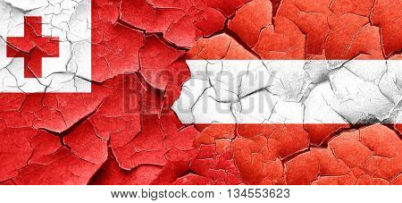 Tonga flag with Austria flag on a grunge cracked wall