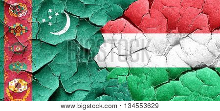 Turkmenistan flag with Hungary flag on a grunge cracked wall