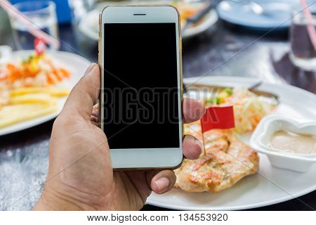Close up of a woman using mobile smart phone in restaurant.