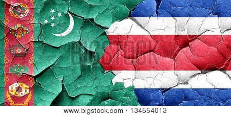 Turkmenistan flag with Costa Rica flag on a grunge cracked wall