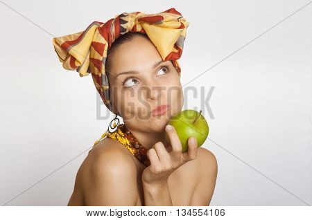 girl in scarf holding a green apple