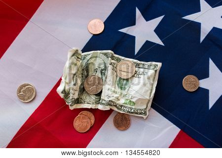 budget, money, finance, financial crisis and nationalism concept - close up of american flag and cent coins with crumpled dollar banknote
