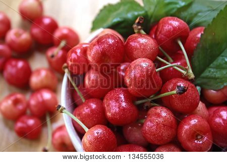 Bowl of fresh red cherries on wooden table