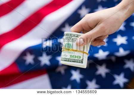 finances, corruption, investment and economics concept - close up of hand with dollar cash money over american flag