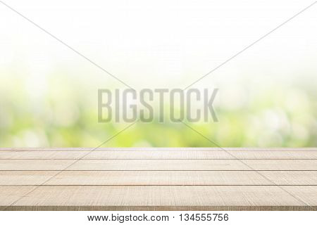 Beige wood table top panel on green nature blurred background use for display or montage products for advertisement in spring environmental concept