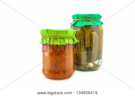 Homemade pickled squash caviar with cucumbers, garlic and onions in glass jar with paper wrapper. Homemade preserves, pickles. Jar of canned marinated cucumbers with squash caviar isolated