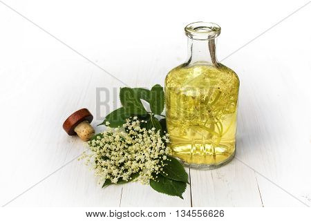 elderflower drink in a glass bottle on a white wooden table syrup for refreshing juice and champagne in summer background fades to white selective focus narrow depth of field