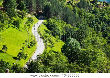 Aerial view of three motorcyclists on a winding rural road through a scenic lush green forested mountain valley