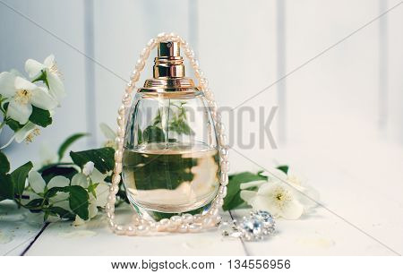 perfume and a string of white pearls
