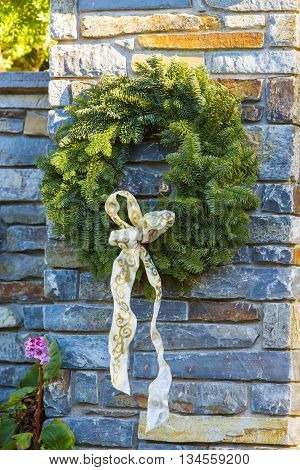 Festive Christmas Advent wreath is hanging outside at stone fense background