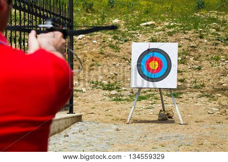 Man taking aim with a crossbow at an outdoor target on a shooting range over the shoulder view with focus to the target
