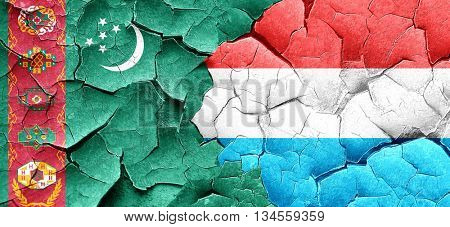 Turkmenistan flag with Luxembourg flag on a grunge cracked wall