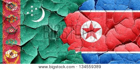 Turkmenistan flag with North Korea flag on a grunge cracked wall