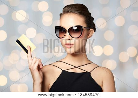 shopping, finances, fashion, people and luxury concept - beautiful young woman in elegant black sunglasses with credit card over holidays lights background