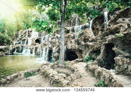 Waterfall in sandy rocks under green trees