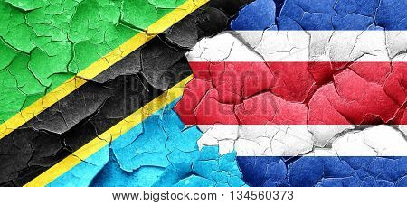 Tanzanian flag with Costa Rica flag on a grunge cracked wall