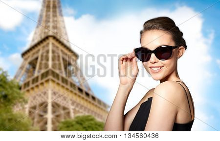 accessories, eyewear, fashion, people and luxury concept - beautiful young woman in elegant black sunglasses over paris eiffel tower background