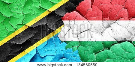 Tanzanian flag with Hungary flag on a grunge cracked wall