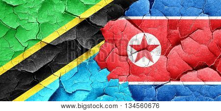 Tanzanian flag with North Korea flag on a grunge cracked wall