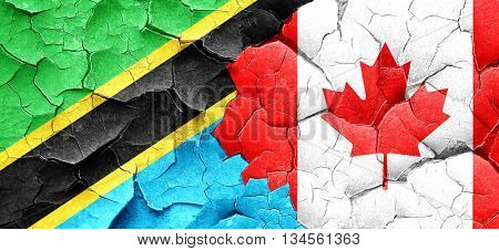 Tanzanian flag with Canada flag on a grunge cracked wall